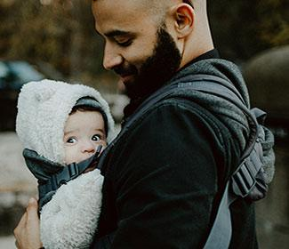 Man holding his baby on his chest with a baby carrier.