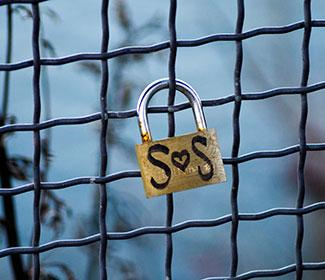 "A lock locked on a fence with ""S heart S"" written on it"