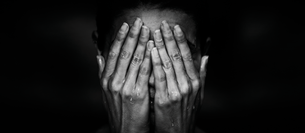 Black-and-white photo of a woman crying, with hands over her face