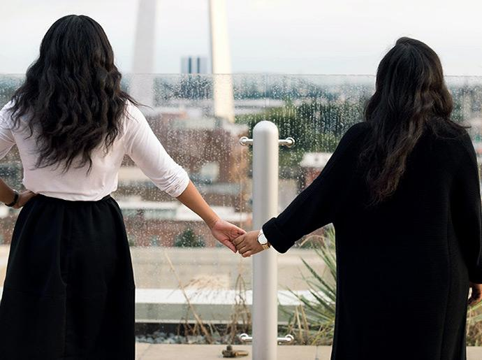 The back of two woman holding hands has they overlook a city