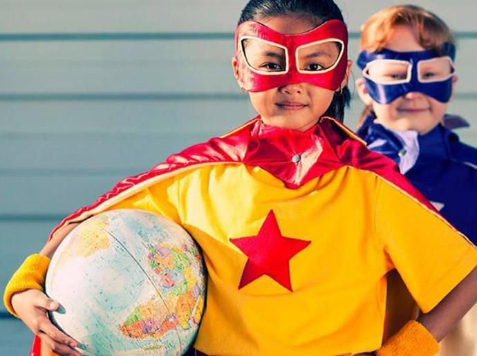 Two girls dressed as superheros, one is holding a globe