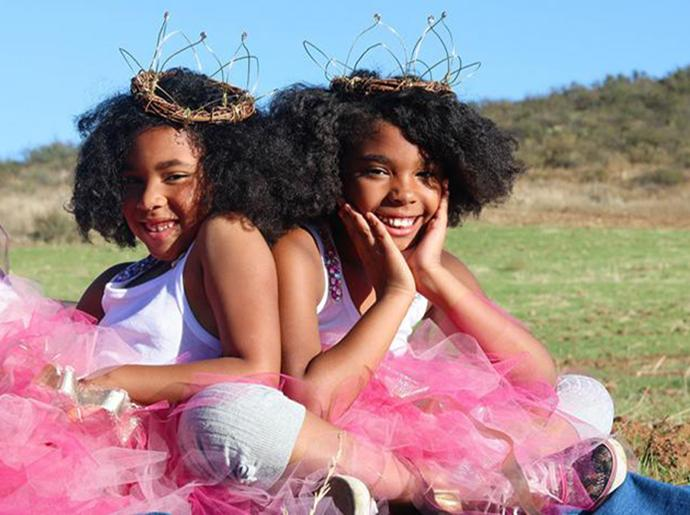 Two girls with tutus sitting outside smiling.