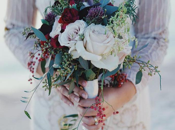 Close up of a bride holding a bouquet of flowers.