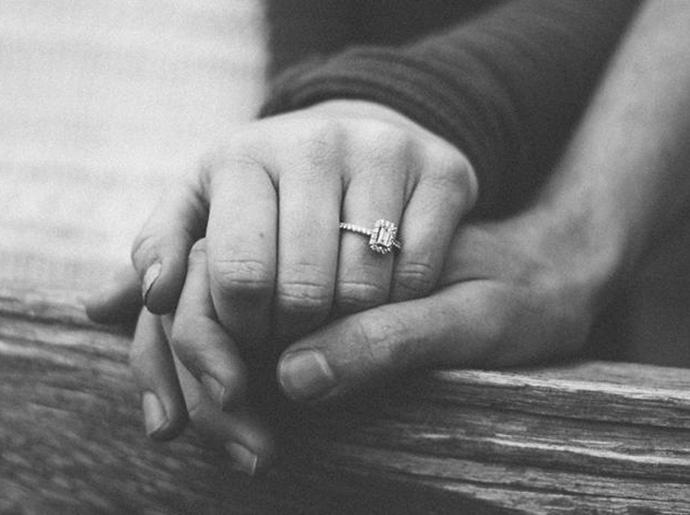 Black and white image of a close up of a married couple holding hands.